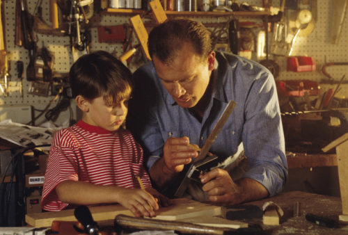 Father showing son woodworking technique