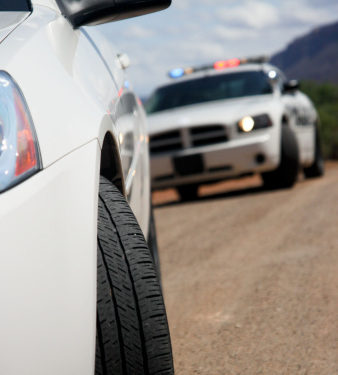 white car stopped by a police officer in a blurred white Dodge Charger patrol car