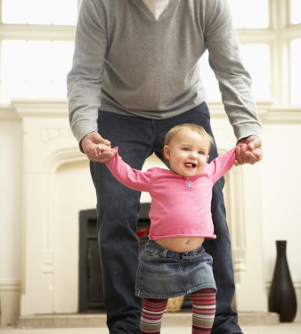 father holding young daughter's hands as she is trying to learn to walk