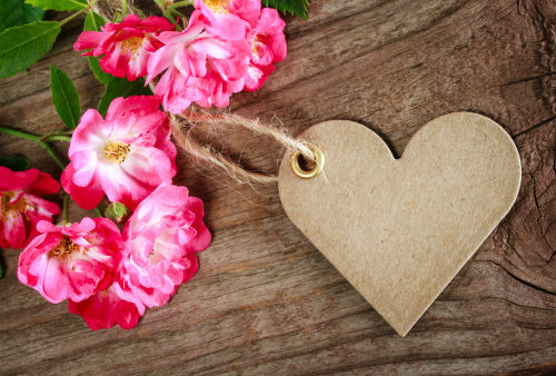 Pink flowers with green leaves near a heart shaped brown paper, as learn more about the life, death and resurrection of Christ