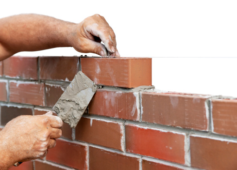 man's hand with trowell constructing a wall of bricks like God is constructing our lives