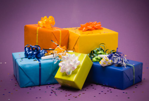 Multi-colored wrapped gifts with bows, ribbons, and confetti