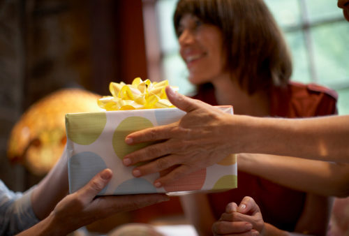 Two women exchanging colorful gift-wrapped box over table as an act of stewardship within their circle of friends