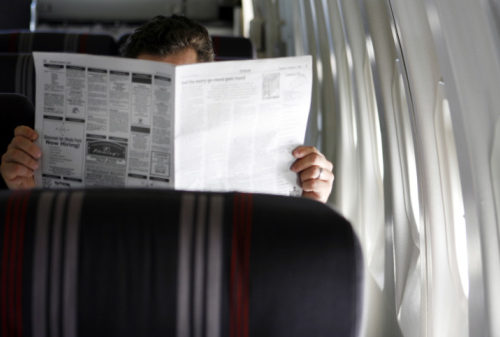 Man reading a newspaper in an airplane