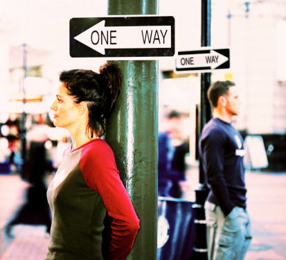 side profile of a woman in the foreground and a man in the background both leaning against green posts with one way traffic signs above their head with each sign facing the opposite direction