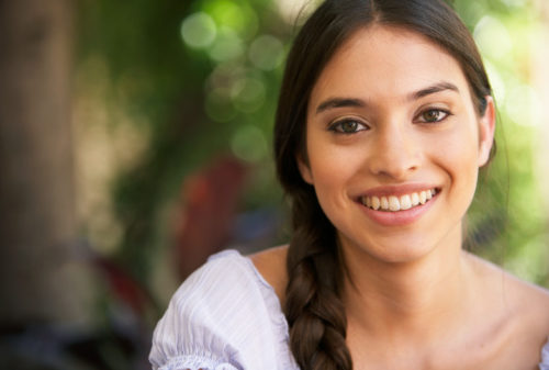close up of a brunette young woman with a big smile showing that she is a happy Christian