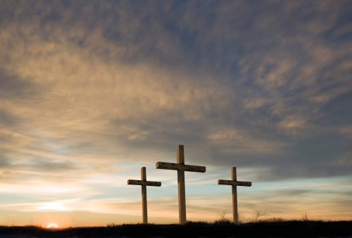 three crosses with beautiful sunrise in the background signifying the morning that Jesus was resurrected and broke the power of sin