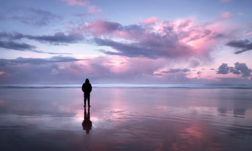 silhouette of a man on a beach with a pink and blue sunset