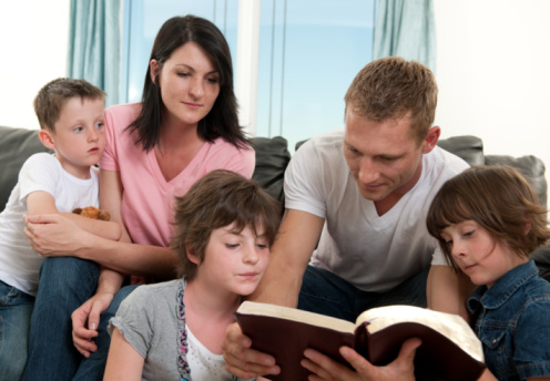 Family gathered around a father reading from the Bible.