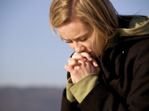 blonde woman in a black wool peacoat sitting outdoors earnestly praying for God to help her forgive
