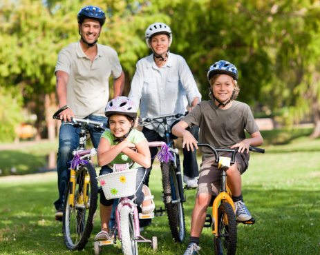 family of four standing with their bicycles outside on a sunny day as they are being active together
