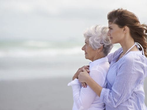 young woman at the seaside embracing the back of her elderly mother who has Alzheimer's