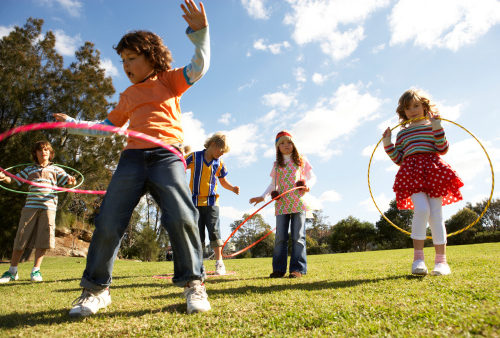 group of children playing on the grass twirling hula hoops around their waists on a sunny day