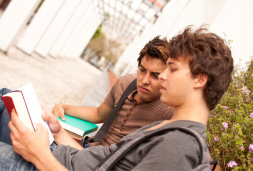 two teenage boys outside a school pensively looking over some books because they know the benefits of learning to read