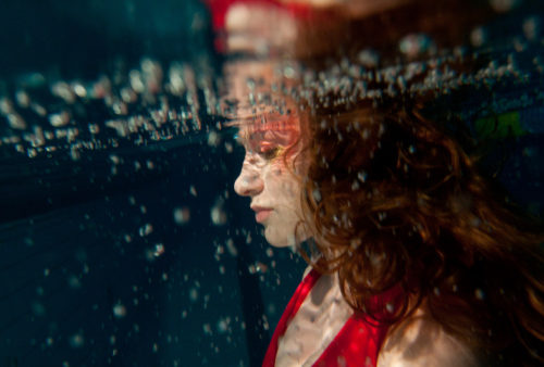 Woman in red under water, as we study about the experience of salvation in Christ, revealed in Scripture