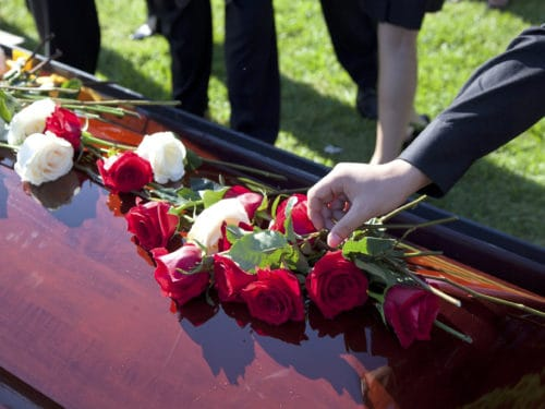 man placing red and white roses on a casket of dead loved one