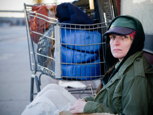 homeless woman sitting beside shopping cart full of belongings wanting to be helped through the service of The Bridge Foundation