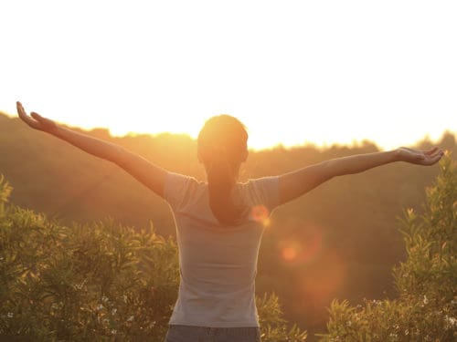 Woman with arms outstretched towards eternal life