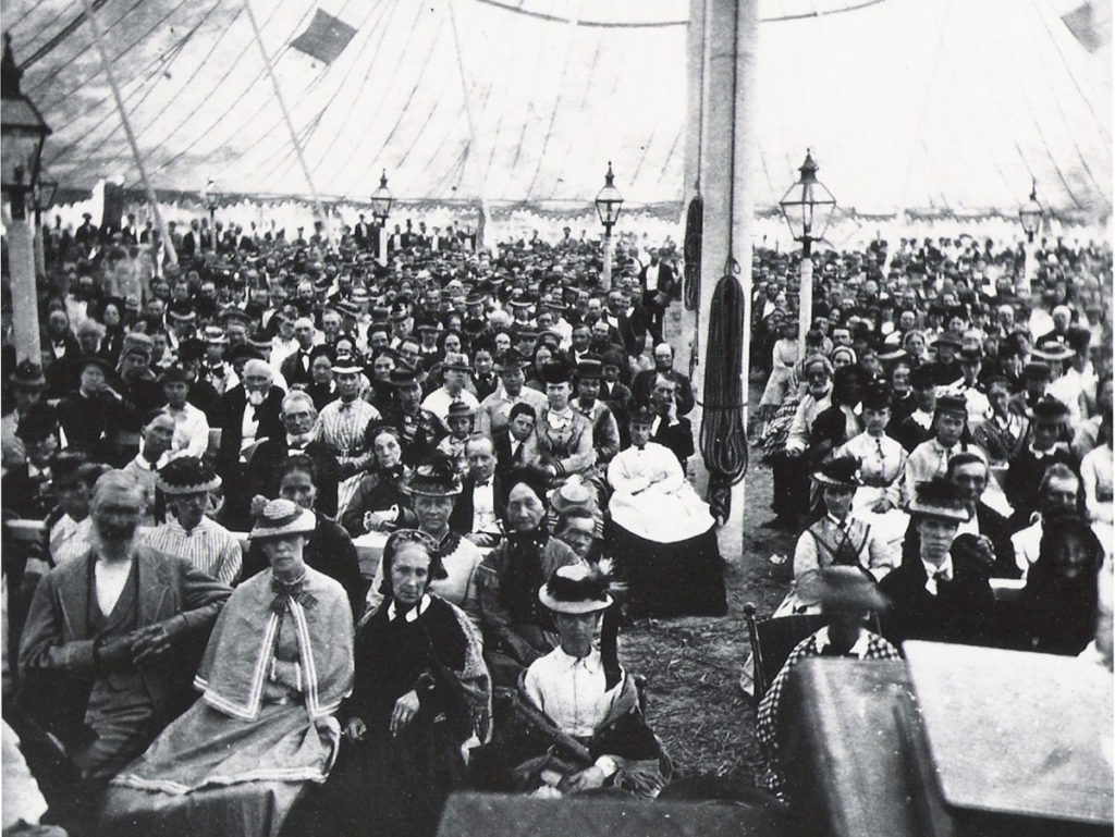Early Seventh-Day Adventist gathered in a large tent for campmeeting