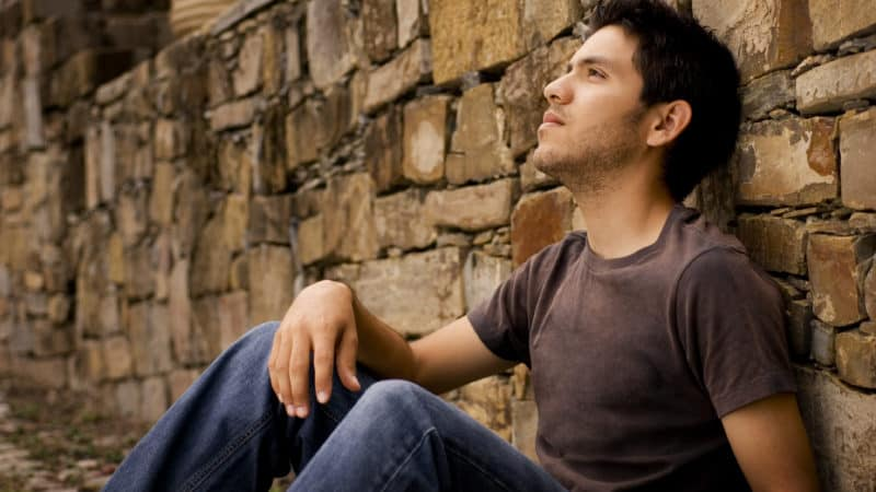 young man sitting against a stone wall wanting to understand the bible better