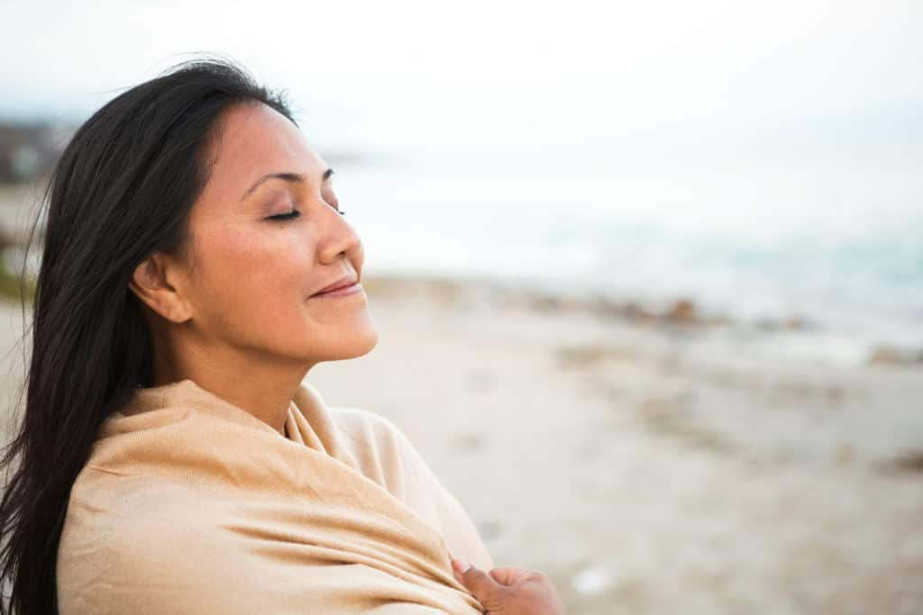 woman at seaside happy that the bible has helped her daily life