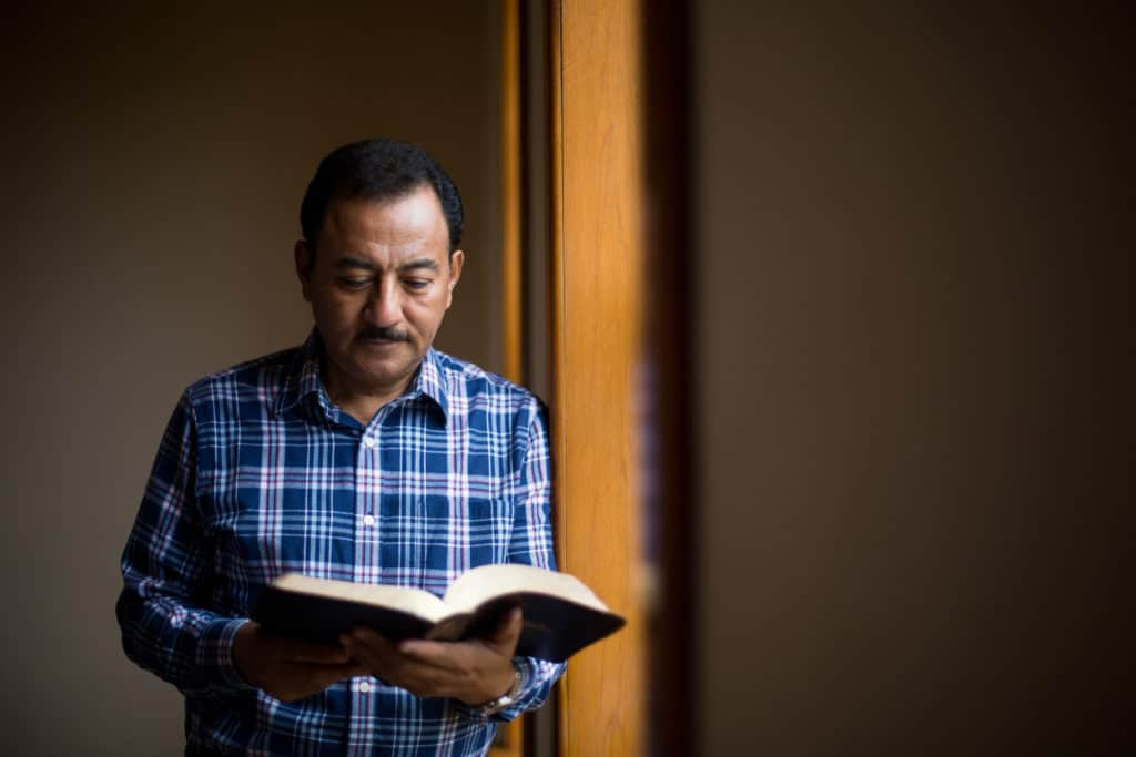 man standing holding an open bible wanting to learn the truth behind bible contradictions