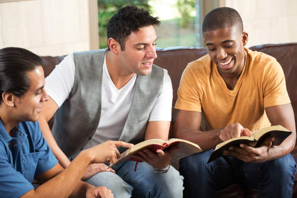 Three men studying the Bible