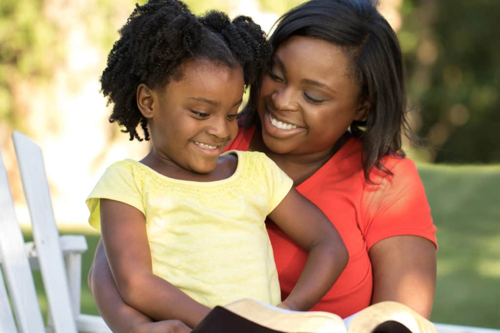 mother and daughter reading the bible to help with their daily life