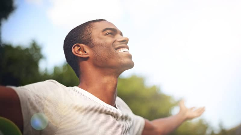 man with arms outstretched because he is happy to understand the bible better