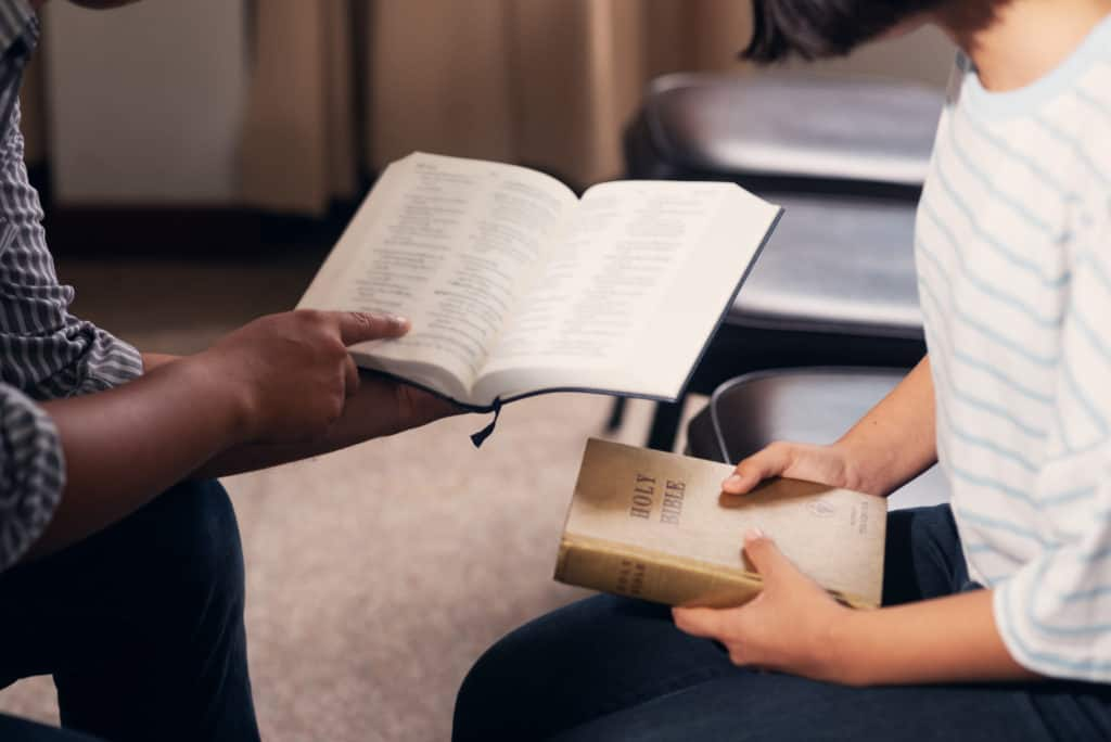 man and women studying poetry in the bible and examining what seems like bible contradictions