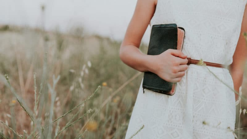 woman in white dress holding bible close because she loves the understanding it brings