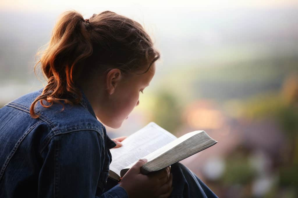 teenage girl sitting outdoors trying to understand her Bible