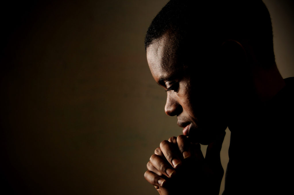 man praying to help discern whether contradictions in the bible are real or not