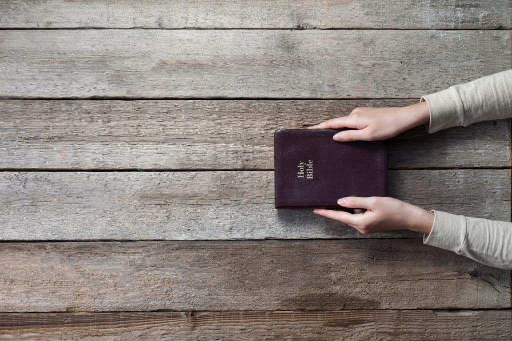 woman sitting at table with closed brown leather bible