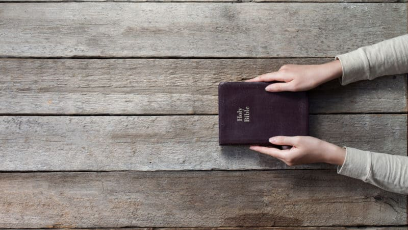 woman holding closed bible on a table hoping to find understanding in its pages
