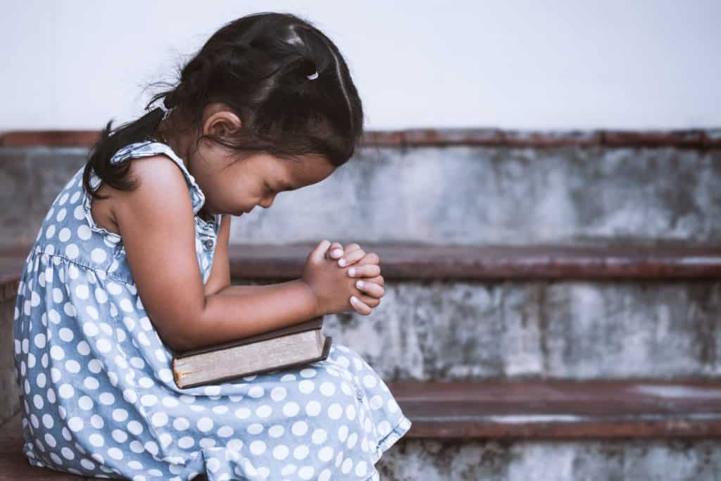 young girl with bible on lap sitting on steps praying