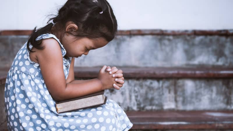 little girl praying that she would understand the bible better