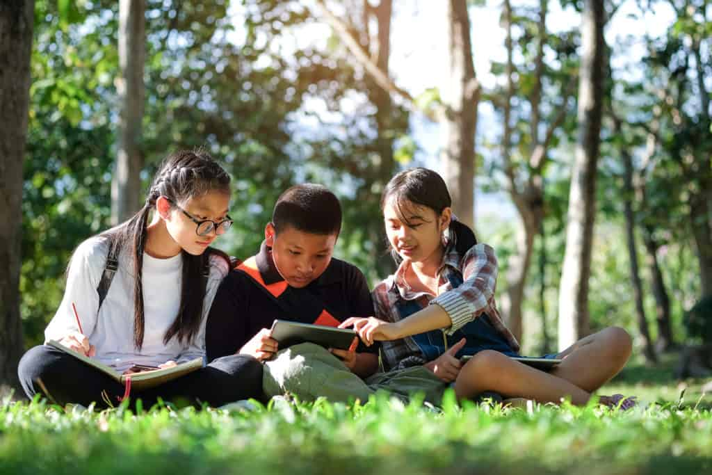 three teens sitting on grass studying how the bible can help them in their daily life