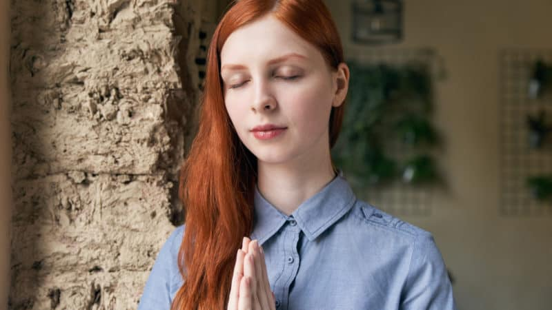 young woman with long red hair saying a prayer to God