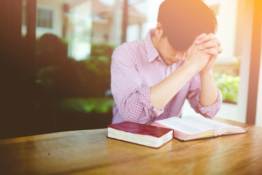 Young man praying with Bible
