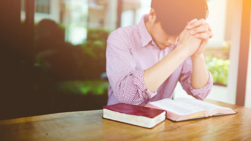 young man sitting at table with open scriptures saying a prayer before beginning bible study