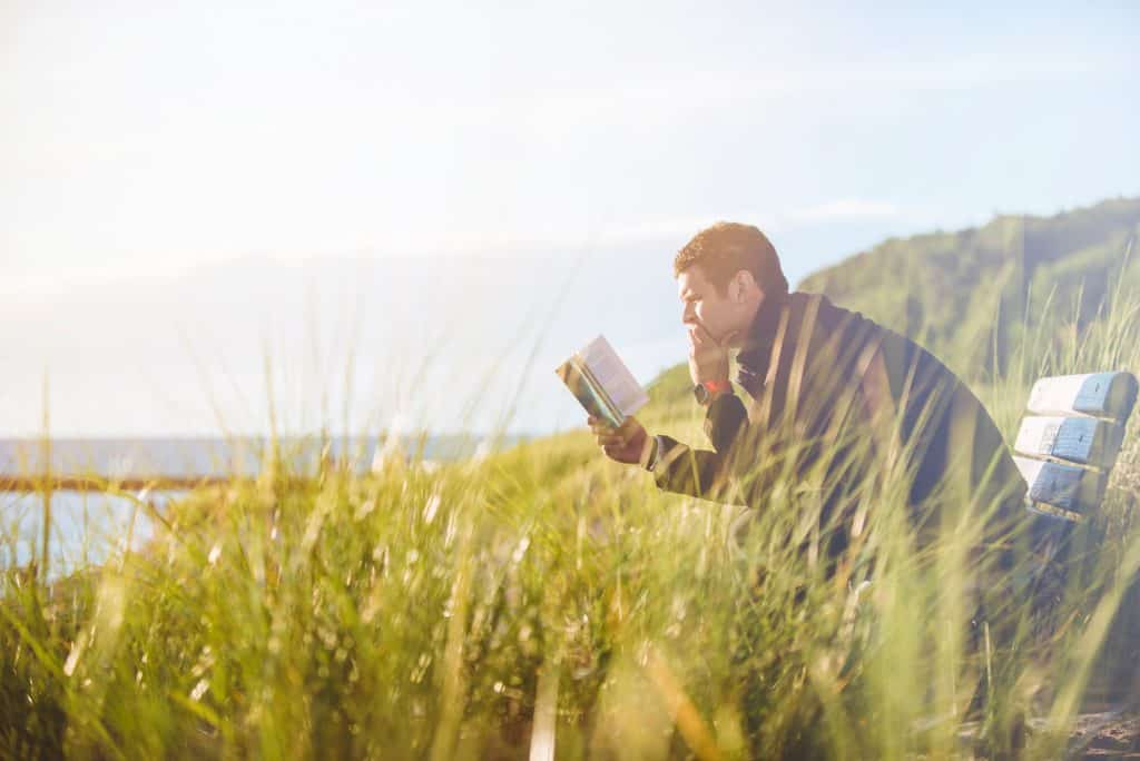 Man sitting outdoors looking at a book