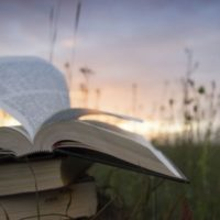 Three Bibles stacked in a field at sunset with the wind blowing through the pages of the open Bible on top.