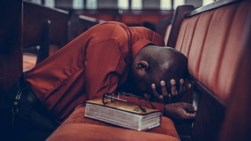 man with Bible kneeling on church pew earnestly in prayer after a bible study
