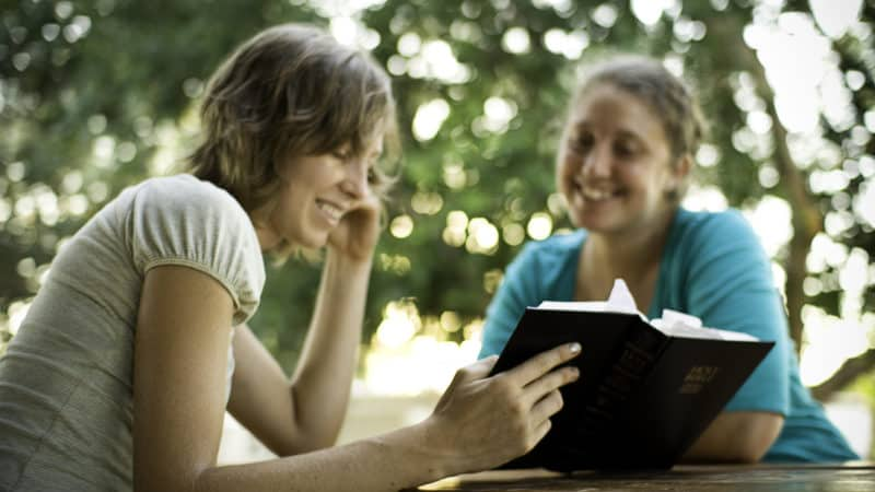 two women sitting outdoors at a picnic table reading the bible together