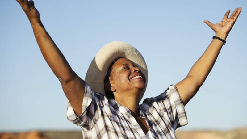 older woman wearing a straw hat and grey and white plaid shirt out in a field with arms raised feeling happy about the gift of salvation through Jesus