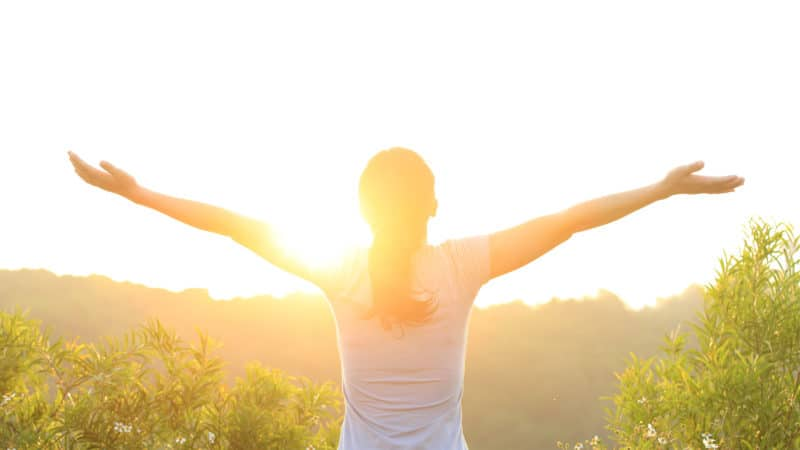 Woman with outstretched arms during golden hour
