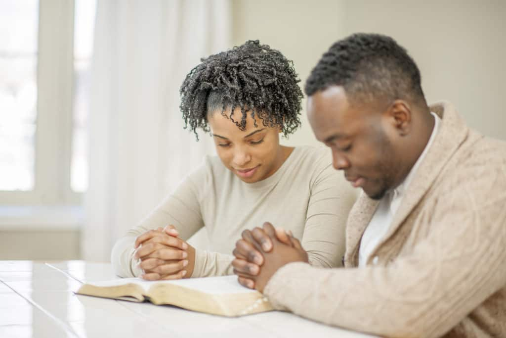 Couple prays with open Bible