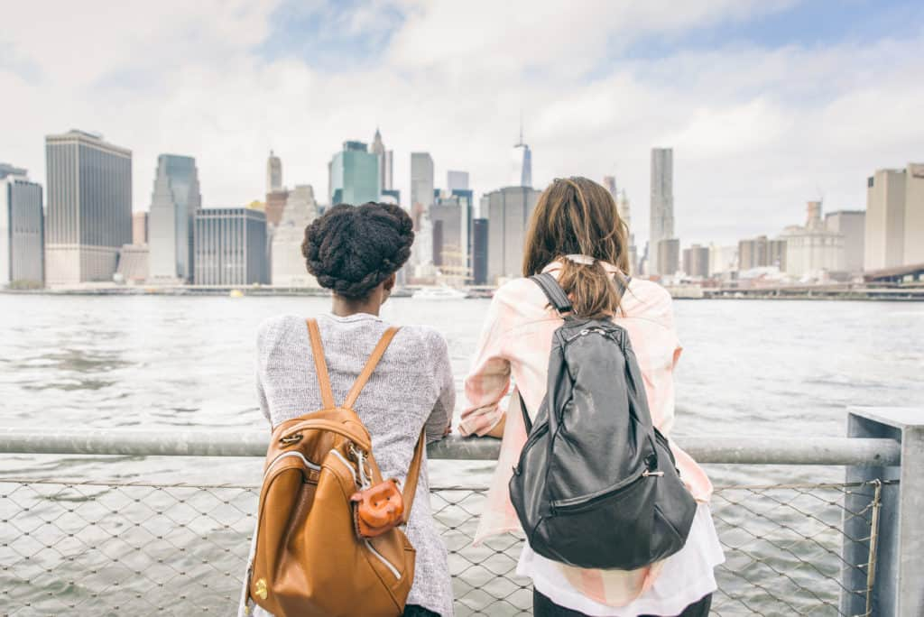 two girls on pier with backpacks looking at cityscape