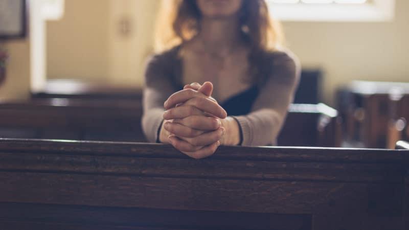 woman praying in church pew on Sabbath